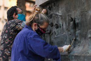 Especialistas trabajan en la restauración de las placas de bronce del monumento de la ex plaza Vélez Sársfield